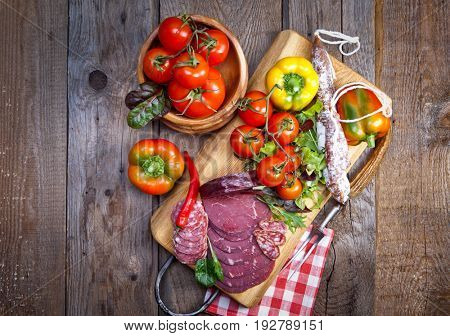 Delicious prosciutto and salami slices on wooden chopping board with vegetables and herbs. Culinary traditional ham.