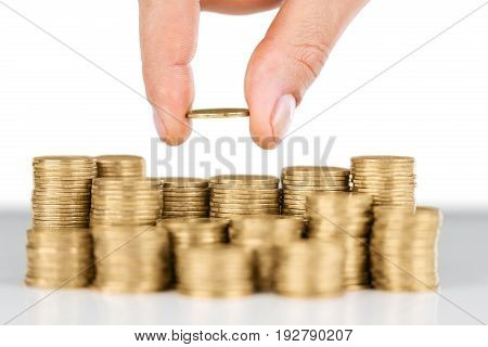 Hand putting coin coins close up blue background