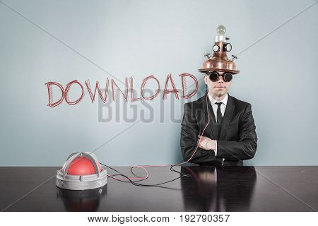 Portrait of confident businessman wearing futuristic helmet while sitting arms crossed by download text on gray wall