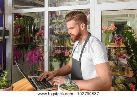 Young handsome florist working with laptop in flower shop