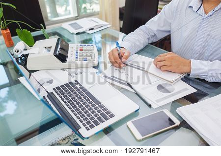 Business Man Working On Laptop And Analysis Data On Paper During Working At Home Office