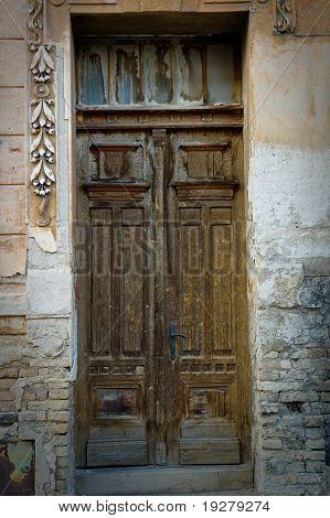 Old broken, damaged door on the classic building