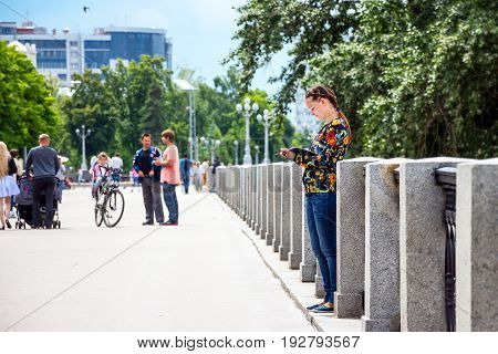 SAMARA, RUSSIA - JUNE 18, 2017: People walking in a park on Maxim Gorky Street. A girl stands in the park and draws in a notebook. Embankment of the Volga River
