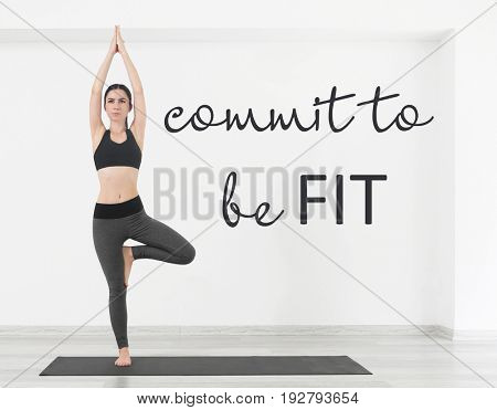 Fitness quotes. Text COMMIT TO BE FIT and young woman practicing yoga on white wall background