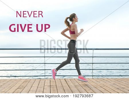 Fitness quotes. Text NEVER GIVE UP on background. Young woman running on pier
