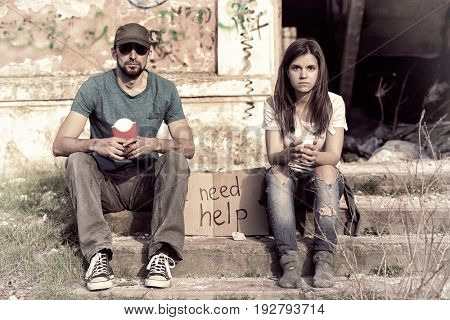 Poverty concept. Poor people sitting on stairs of abandoned building