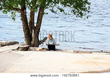 SAMARA, RUSSIA - JUNE 18, 2017: Woman artist draws a picture sitting on the banks of rivers