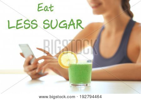 Fitness quotes. Text EAT LESS SUGAR, glass of smoothie and young woman on background