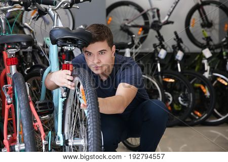 Young man checking bicycle wheel in shop