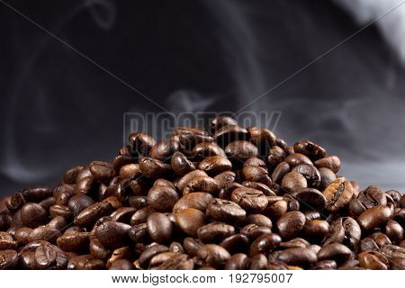 roasted coffee beans with smoke on a dark background