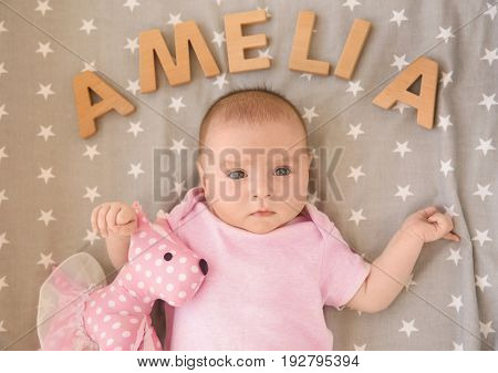 Cute baby lying on bed with toy and word AMELIA composed of wooden letters. Choosing name concept