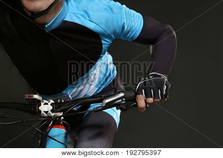 Young sporty cyclist riding bicycle on dark background, closeup