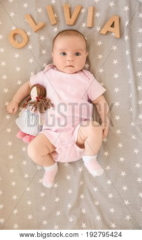 Cute baby lying on bed with toy and word OLIVIA composed of wooden letters. Choosing name concept