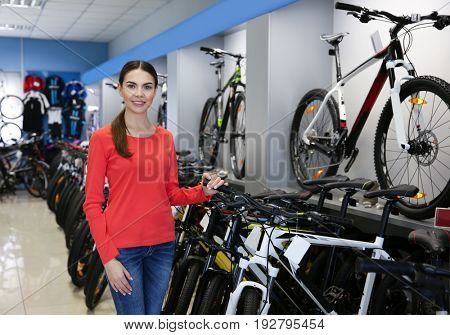 Smiling young woman standing in bicycle shop