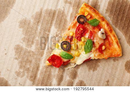 Slice of tasty pizza on carton background
