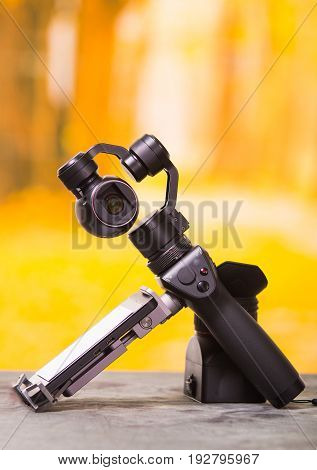 QUITO, ECUADOR- DECEMBER 22, 2017: Osmo Mobile gimbal, new generation of electronic stabilizer over a wooden table in a blurred forest background.