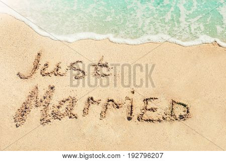 Text JUST MARRIED written on sand near water. Honeymoon concept