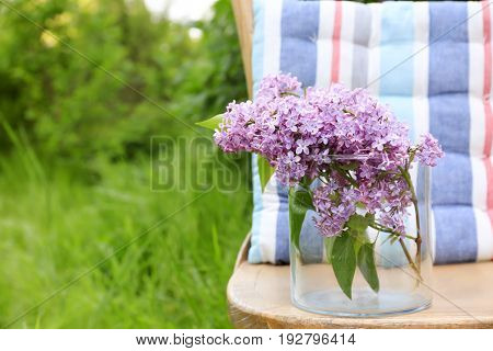 Lilac flowers on chair in garden