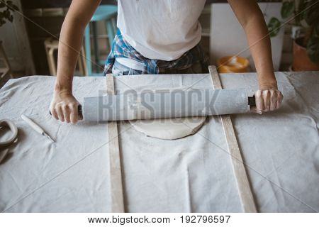 Artist rolls raw clay using big grey rolling pin on table covered with industrial fabric in workshop