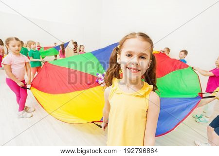 Close-up portrait of smiling little girl playing parachute games with her friends in gym