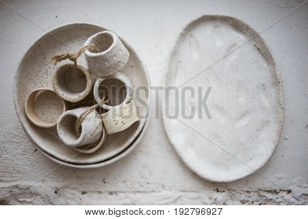 Top view on two grog clay plates with beautiful rustic napkin rings on white background