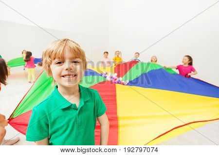 Close-up portrait of blond six years old boy playing rainbow parachute together with his friends