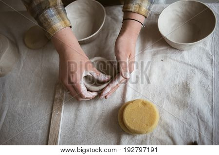 Woman's hands makes clay ware in pottery workshop top view