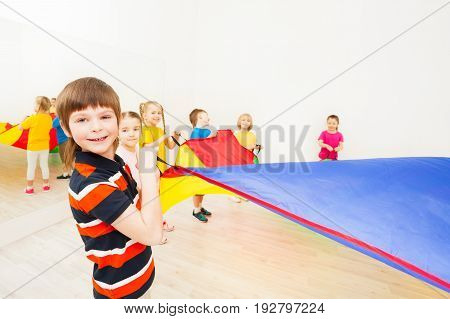 Portrait of smiling kid boy playing colorful parachute with friends in gym