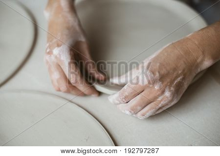 Woman's hands makes clay plates in pottery workshop top close up view; focus on stained hand