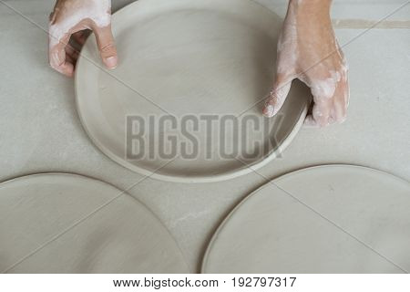 Woman's hands makes raw clay plates round shape in pottery studio close up top view