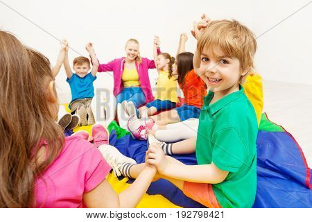 Portrait of smiling blond preschool boy playing circle games, sitting on rainbow parachute and holding hands with friends