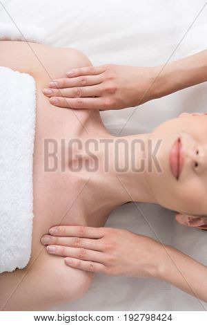 Feeling relaxed. Close up top view of shoulders of young woman with fresh and clean skin, which is lying on table and getting body massage in spa salon. Selective focus