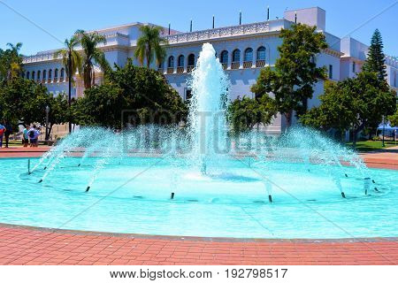 June 20, 2017 in San Diego, CA:  Large water fountain with museum buildings beyond taken at Balboa Park where people can visit museums and admire the gardens and architectural designs taken in San Diego, CA