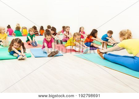 Portrait of female coach teaching kids doing warming-up during gymnastics