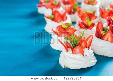 A small meringue Pavlova dessert with some strawberry slices with mint leaves