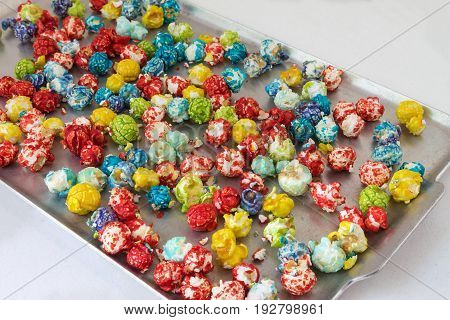 horizontal image of a bunch of multicolored popcorn baked in a silver cookie sheet on white background