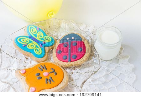horizontal image of three cookies decorated as a lady bug and a blue butterfly and the face of an orange cat accompanied by a small glass of milk.
