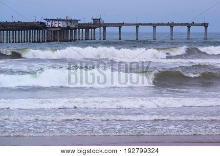 June 19, 2017 in Ocean Beach, CA:  Waves crashing onshore with a large concrete pier beyond where locals and tourists can walk, fish, and have a meal at the café on the pier taken in Ocean Beach, CA