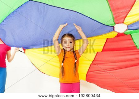 Portrait of preschool girl standing under the tent made of parti-colored parachute with her hands up
