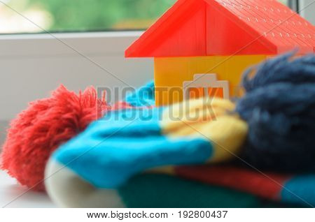 Toy house on the window sill wrapped in a scarf. Warming up the house