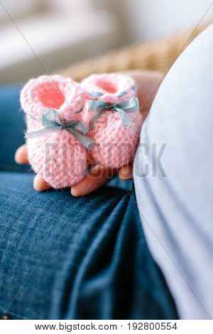 future mother knows a sex of her baby. Pregnant woman holding pink knitted baby bootees at a stomach with selective focus close up.