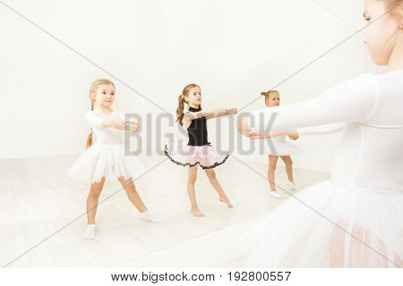 Three adorable girls practicing ballet near the mirror in light dance studio