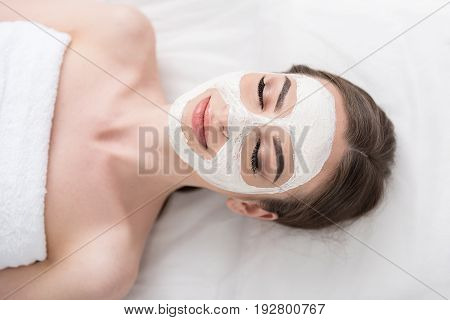 Relaxed and delighted. Top view of charming lady is lying on couch with white mask and closed eyes while reveling in spa procedure