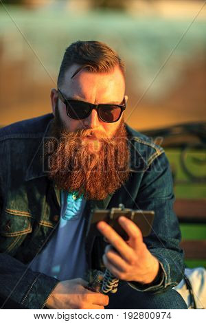 Bearded Gadget Man In Sunglasses. A Brutal Young Guy With A Large Beard Is Surfing On The Internet O