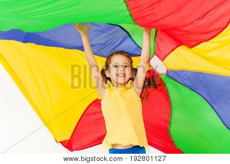 Happy six years old girl jumping under canopy made of party-colored parachute, raising her hands up