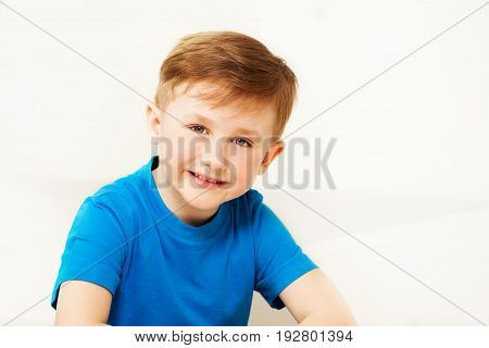 Close-up portrait of happy schoolboy in blue t-shirt looking at camera in light studio