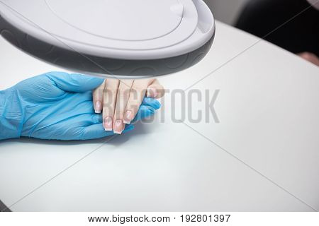 Nails health. Specialist is sitting at workplace in blue gloves. Close up top view of hands of client and professional manicurist. Copy space in the right side