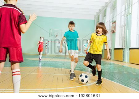 Portrait of 9 years old boy striking the ball during football game in sports hall