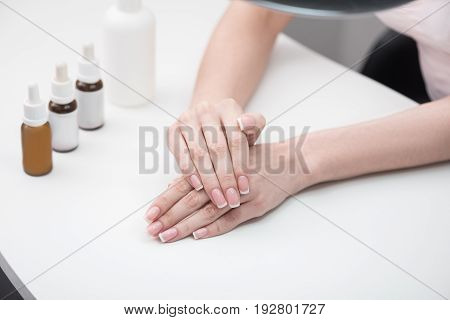 Young woman is sitting at table. Close up of beautiful fingernails with french manicure of girl. Professional care on the background