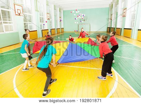 Preteen children playing parachute games, throwing colorful balls in the air, during sports festival in school gymnasium